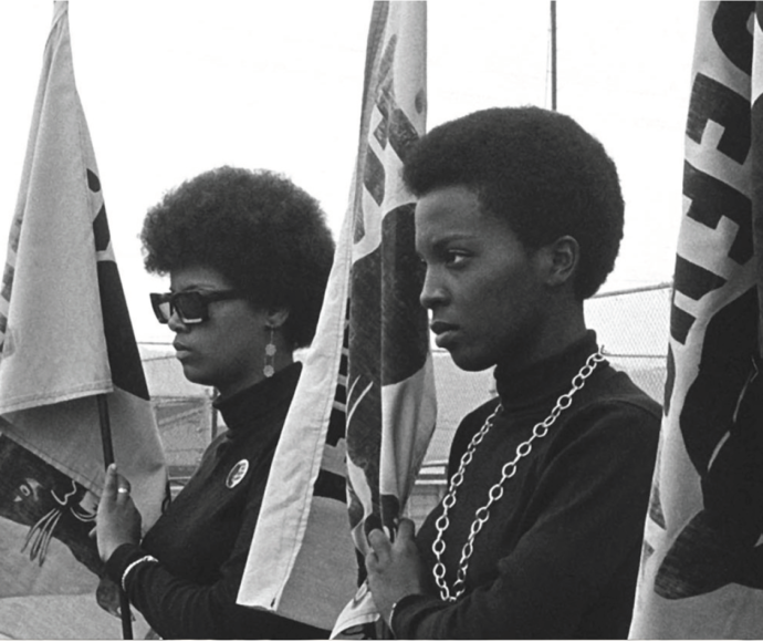 women of the Black Panther Party holding flags