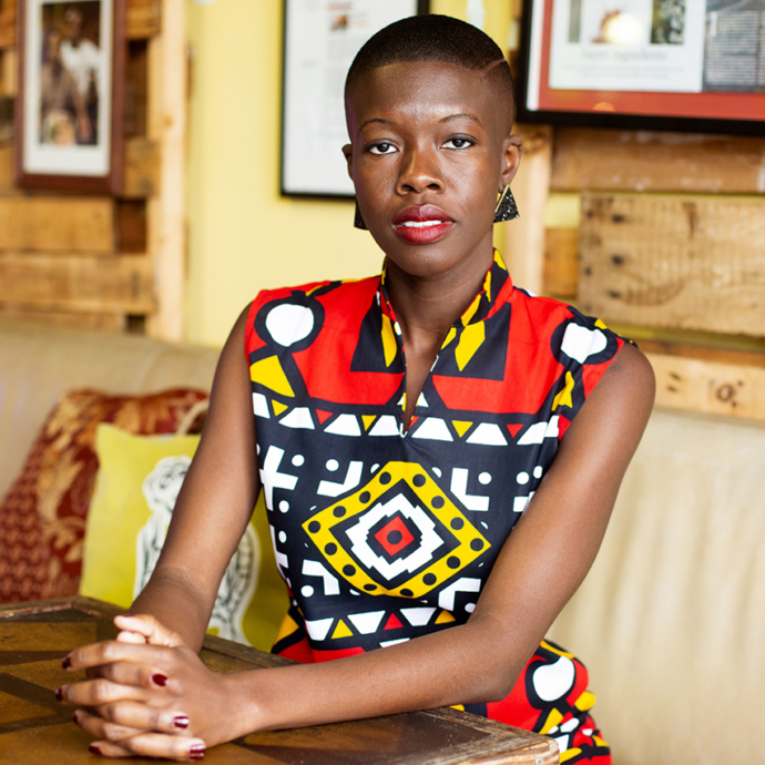 Nadege Green seated, wearing a bold graphic print of red, yellow, black, and white