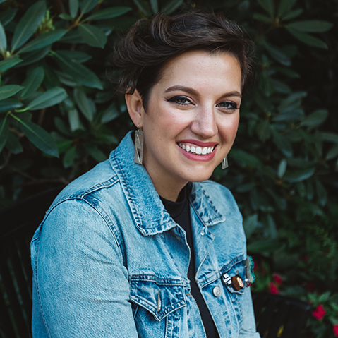 Adrienne Keene wearing a denim jacket in front of a verdant background. Headshot by Brittany Taylor.